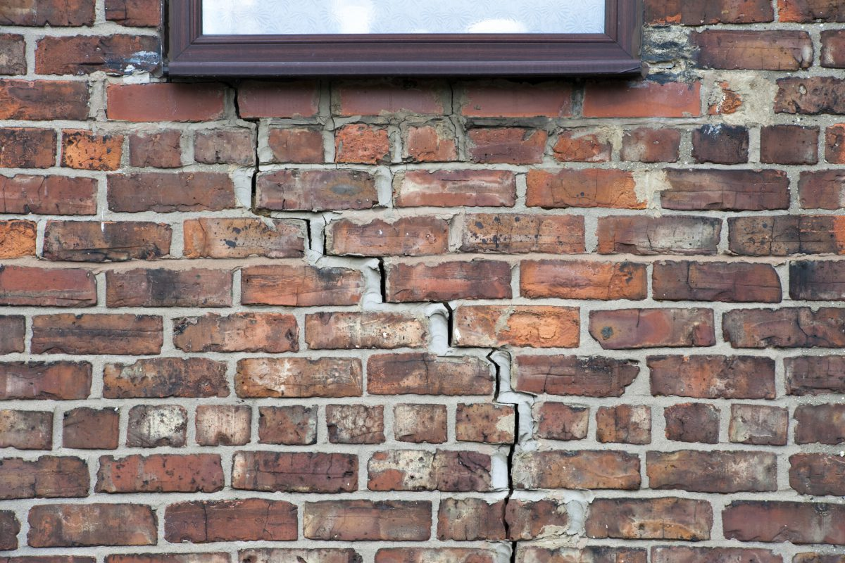 Step cracking damage to brickwork in a wall beneath a window as a result of subsidence.